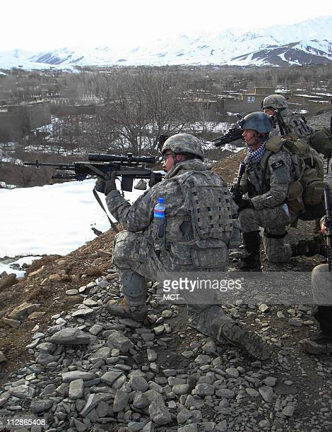 A US Army sniper looks through his rifle's scope to check out a dark shape on a nearby mountainside that turned out to be a large rock