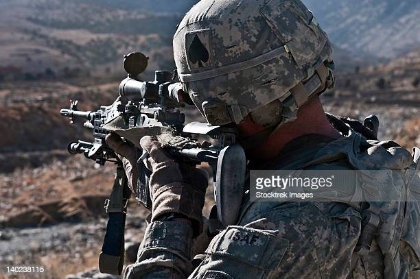 U.S. Army sniper scans a village in Afghanistan for Taliban activity.