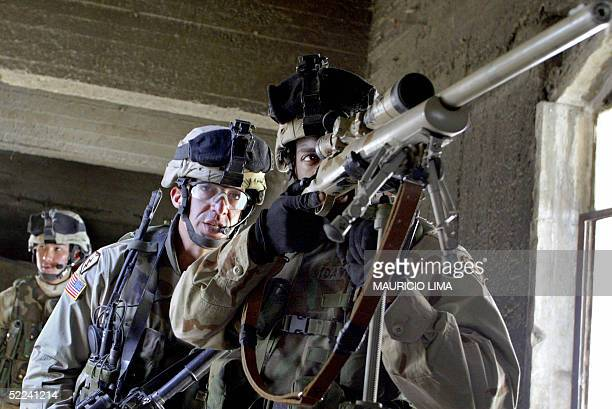 Army sniping team from the 1st Battalion 24th Infantry Regiment scan the area during a joint traffic checkpoint with US Marines and Iraqi soldiers on...
