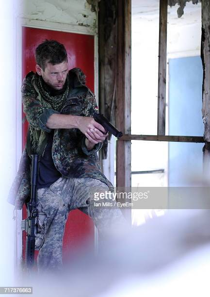 Army Soldier Aiming Gun By Window At Weathered Building