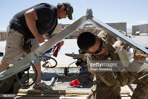 Army soldier and a civilian contractor check a US Army 14' Shadow surveillance drone after it lands at Forward Operating Base Shank May 8, 2013 in...