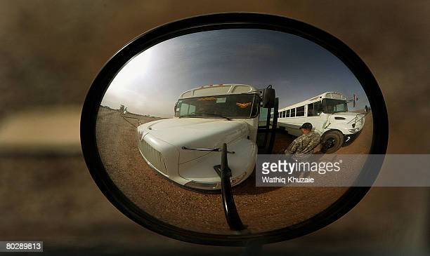 Army soldier and buses are reflected in the wing mirror of a car at Besmaya Range Complex on March 18 northeast of Baghdad Iraq where a graduation...