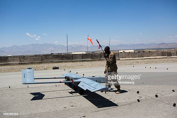 Army soldier checks a US Army 14' Shadow surveillance drone after it lands at Forward Operating Base Shank May 8, 2013 in Logar Province,...