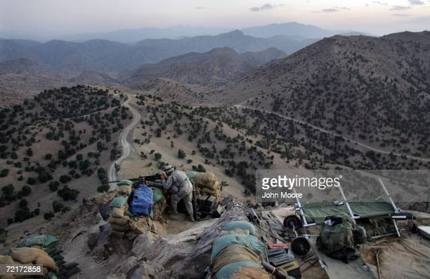 S Army soldier checks the sights of machine gun atop an American outpost October 15 2006 near Camp Tillman Afghanistan just two kilometers from the...