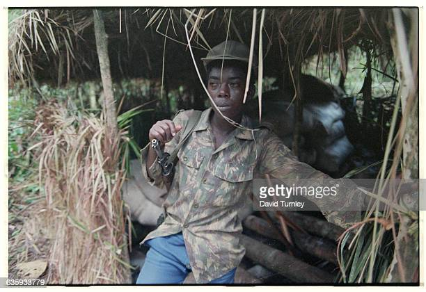 NRA army soldier David Mugamba stands in front of his hut at the Namugongo Political Indoctrination School | Location Near Kampala Uganda