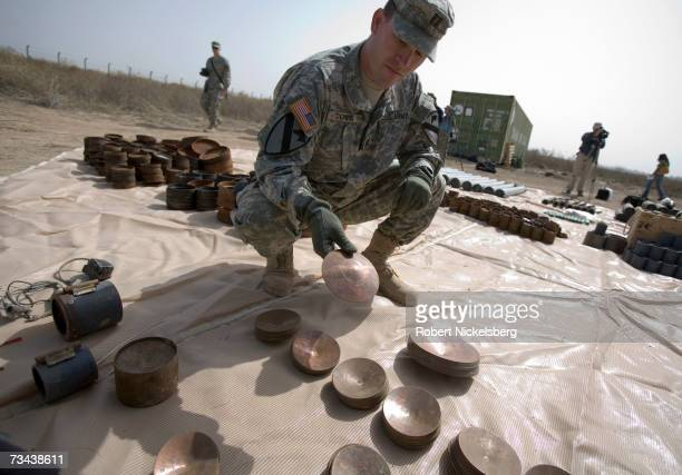 Army soldier displays a large weapons cache of deadly armor-piercing bombs of a type Tehran has allegedly smuggled to Shiite militias, February 26,...