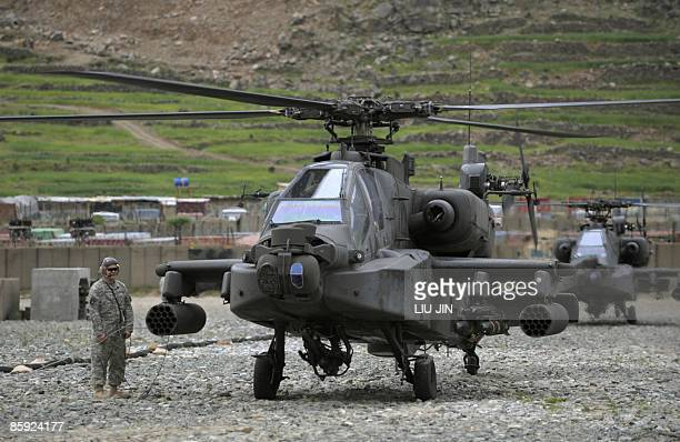 Army soldier from 101 Airborne Division stands beside an AH-64 Apache helicopter refilling at the ISAF's Camp Bostick in Naray, in Afghanistan's...