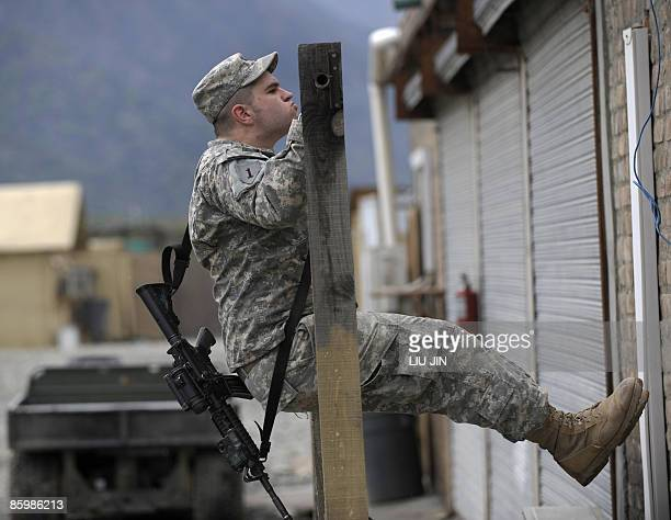 Army soldier from 1st Infantry Division does chin-ups at ISAF's Camp Bostick in Naray, in the eastern Kunar province on April 15, 2009. Afghanistan...