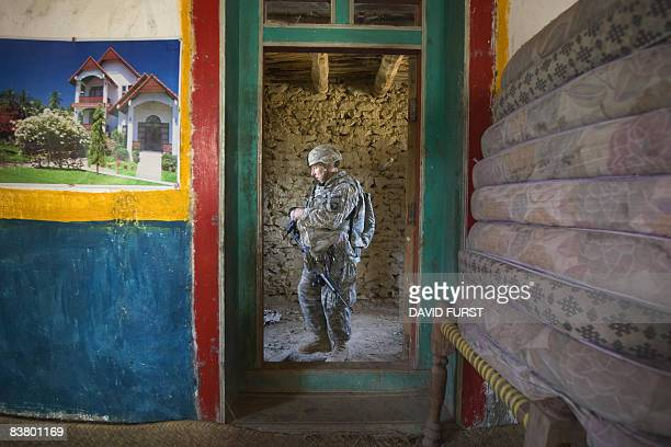 Army soldier from 2-506 Infantry 101st Airborne Division pauses in the doorway of an Afghan home while searching the premises during Operation Shir...