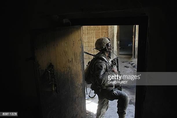 Army soldier from 2-506 Infantry 101st Airborne Division stands in a doorway of an Afghan home during day two of Operation Shir Pacha into the...