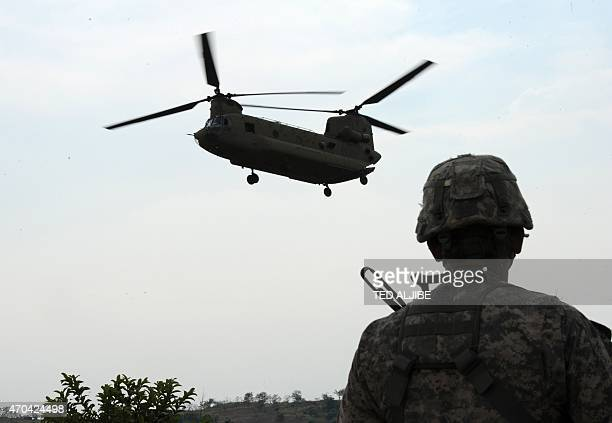 A US army soldier from 2nd Stryker Brigade Combat of the 5th Infantry Division based in Hawaii watches while a US army CH47 Chinook helicopter...