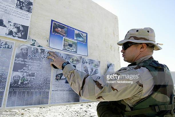 Army soldier from a newly formed Provisional Reconstruction team pastes posters written in Pashtu language seeking information about Osama bin Laden...