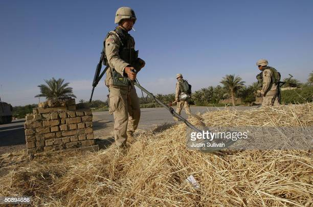 S Army soldier from Alpha Company 1st Engineer Battalion uses a metal detector to search for buried weapons May 25 2004 in Ramadi Iraq Alpha Company...