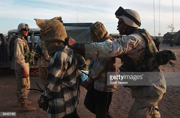 S Army soldier from Alpha Company of 1st Battalion 14th Regiment of the 25th Infantry Division leads away two detainees suspected of being illegal...