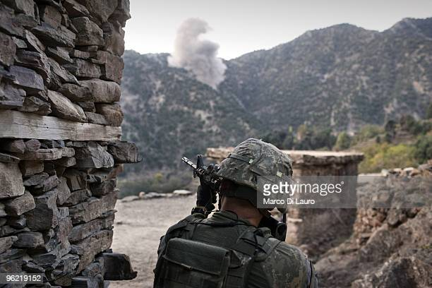 Army soldier from B Company, 2nd Battalion,12th Infantry Regiment, 4th Brigade,4th Infantry Division Baker Company is seen in the foreground of an...