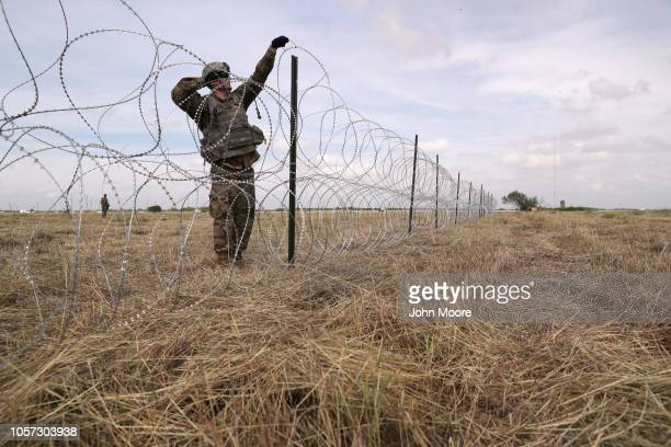 S Army soldier from Ft Riley Kansas strings razor wire near the port of entry at the USMexico border on November 4 2018 in Donna Texas President...