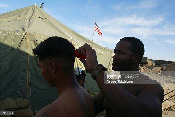 A US army soldier from the 101st Airborne gets a haircut from a fellow soldier at Bagram Air Base April 10 2002 in Afghanistan There are...