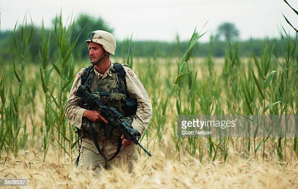 S Army soldier from the 1st Battalion 14th regiment of the 25th Infantry Division advances through an open field during a battle against militiamen...