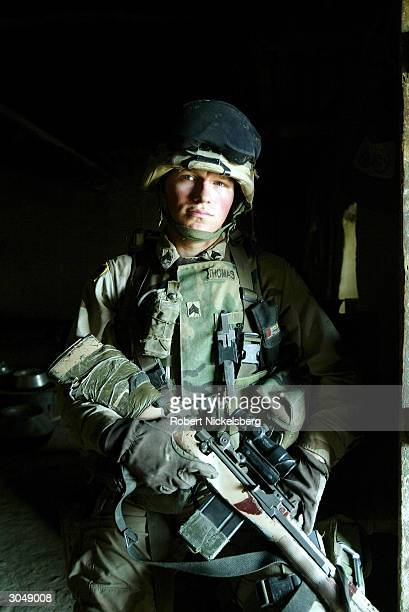 A US Army soldier from the 1st Battalion 501 Parachute Infantry Regiment stands in a doorway on watch as a team of soldiers searches a villager's...