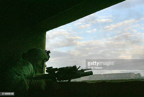 S Army soldier from the 1st Infantry Division's 2nd Battalion2nd Regiment tries to identify an enemy position while engaging enemy forces in heavy...