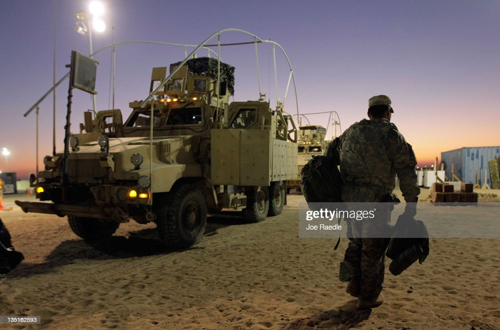 A U.S. Army soldier from the 2-82 Field Artillery, 3rd Brigade, 1st Cavalry Division, carries his gear after arriving in Kuwait from Camp Adder in Iraq on December 7, 2011 at Camp Virginia, near Kuwait City, Kuwait. After seven months in Iraq, the 3rd Brigade has pulled out of the country as part of America's military exodus by the end of December after eight years of war and occupation which included the overthrow of Saddam Hussein.