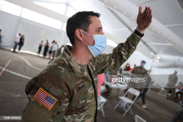 Army soldier from the 2nd Armored Brigade Combat Team, 1st Infantry Division, directs people for immunization with the COVID-19 vaccine at the Miami...