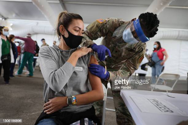 Army soldier from the 2nd Armored Brigade Combat Team, 1st Infantry Division, immunizes Mariana Nascimento with the Pfizer COVID-19 vaccine at the...