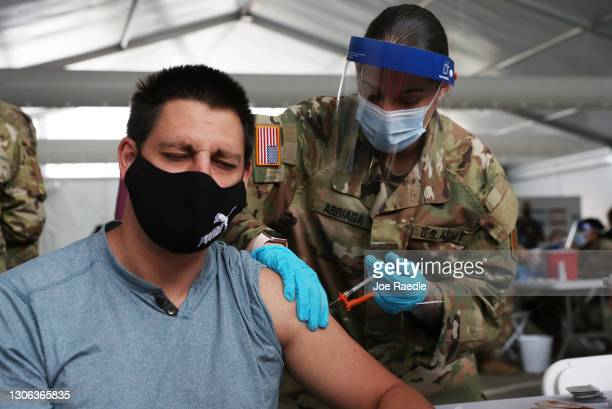 Army soldier from the 2nd Armored Brigade Combat Team, 1st Infantry Division, immunizes Max Pietro with the Johnson and Johnson COVID-19 vaccine at...