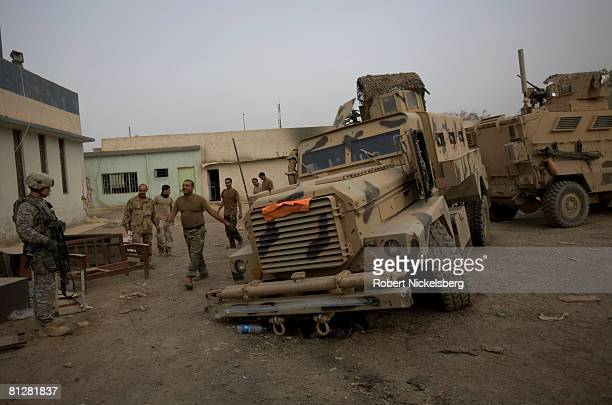 Army soldier from the 3rd Brigade Combat Team 4th ID left watches an an Iraqi Army soldier circles one of his unit's broken down Mine Resistant...