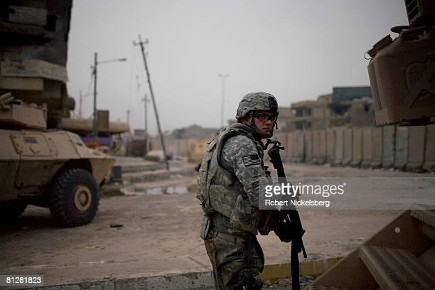 Army soldier from the 3rd Brigade Combat Team 4th ID looks and listens for an enemy sniper firing across the 12' concrete barrier along Al Quds...