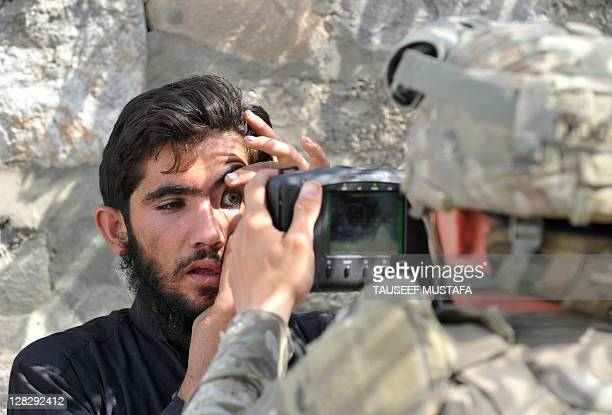 A US army soldier from The HHB 37 Field Artillery Regiment 3rd Bct 25th ID scans the eyes of an Afghan resident with an Automated Biometric...