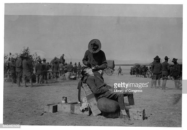 US Army soldier gets a shave using bed rolls and cartridge cases as a barber chair during the United States Army Punitive Expedition to Mexico in...