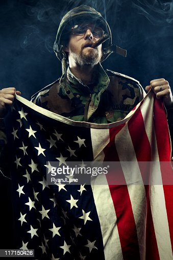 Army Soldier Holding American Flag With Cigar Stock Photo