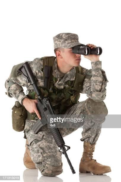 Army soldier holding machine gun and looking through binoculars