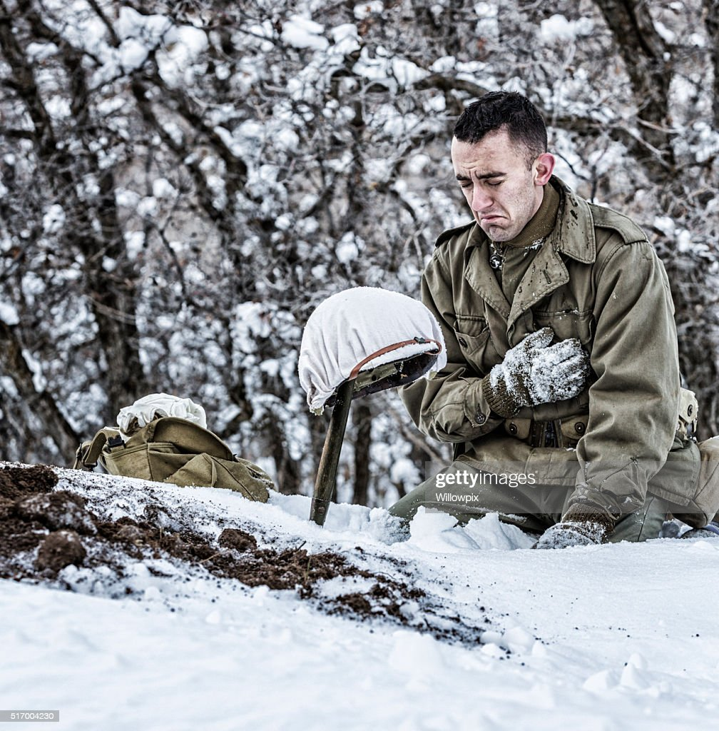 WWII US Army Soldier Kneeling Crying Mourning For Dead Buddy : Stock Photo