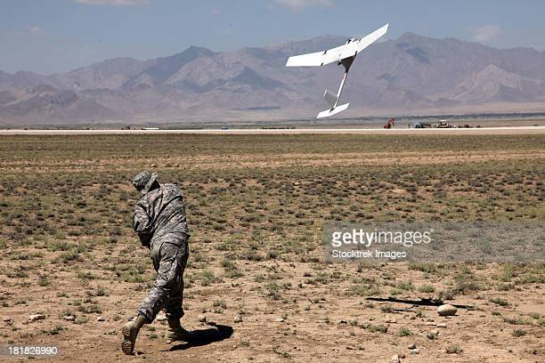u.s. army soldier launches an rq-11 raven unmanned aerial vehicle. - military drones stock pictures, royalty-free photos & images