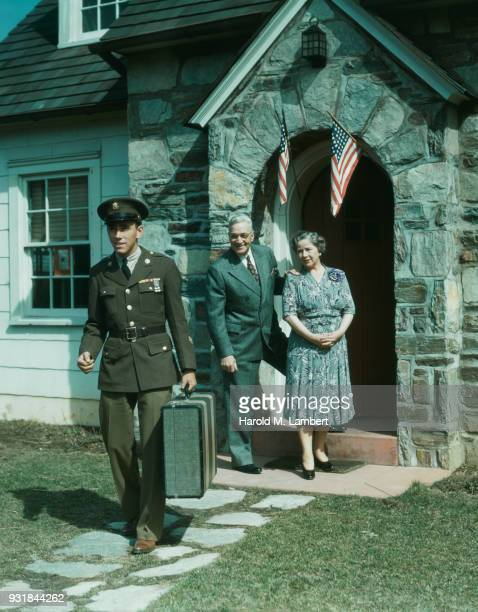 Army soldier leaving his home while parents standing at doorstep