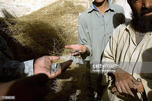 Army soldier, left, examines pieces of shrapnel local Afghan villagers collected after being caught in two cross fires between attacking Taliban and...