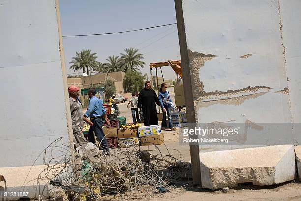 Army soldier looks through a missing concrete barrier wall as residents of Sadr City walk past in Sadr City the 25 million Shia dominated stronghold...