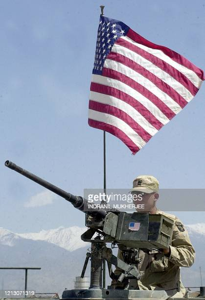 Army soldier mans a 50 callibre machine gun as he stands guard near the runway at the Bagram Air Base 06 May 2002 some 60 kms north of Kabul....