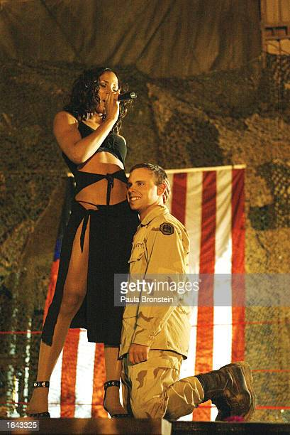 S Army soldier Merlin Culver from Glidell Louisianna gets a hug on stage by one of the cheerleaders during a show put on by the Washington Redskin...