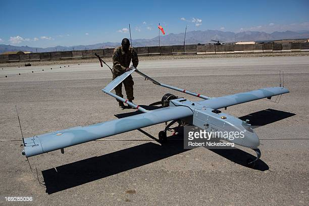 Army soldier moves a US Army 14' Shadow surveillance drone after it lands at Forward Operating Base Shank May 8, 2013 in Logar Province, Afghanistan....