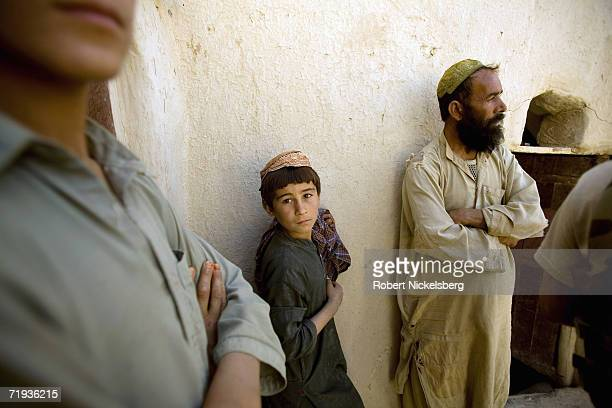 Army soldier, not shown, speaks to local Afghans whose house is often in the crossfire between attacking Taliban and the US Army inside the nearby...