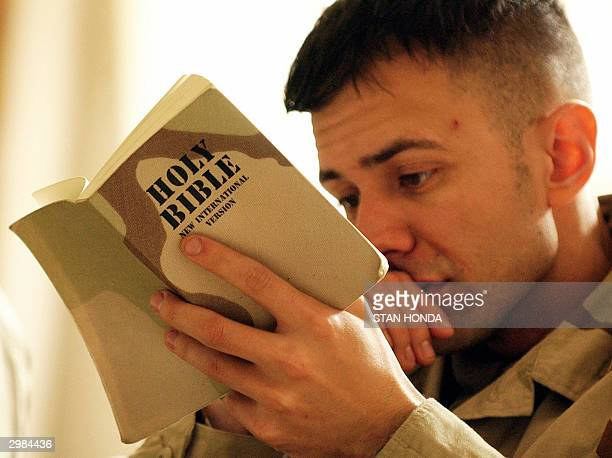 Army soldier of the 1-22 Battalion, 4th Infantry Division, reads from a military bible with a camoflage cover at a general Christian worship service,...