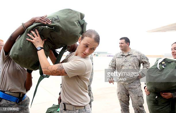 A US army soldier pack their luggage onto an airplane as they prepare to fly out of Iraq on their way home from the alAsad Air Base west the capital...