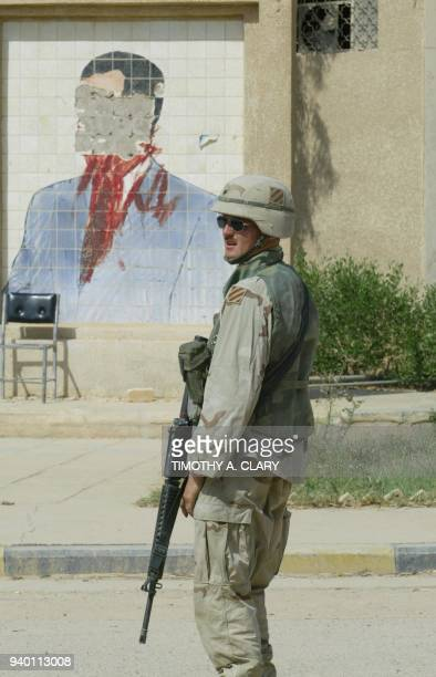 Army soldier patrols near a defaced portrait of toppled leader Saddam Hussein 10 June 2003 the flashpoint town of Fallujah 50 kms west of Baghdad US...