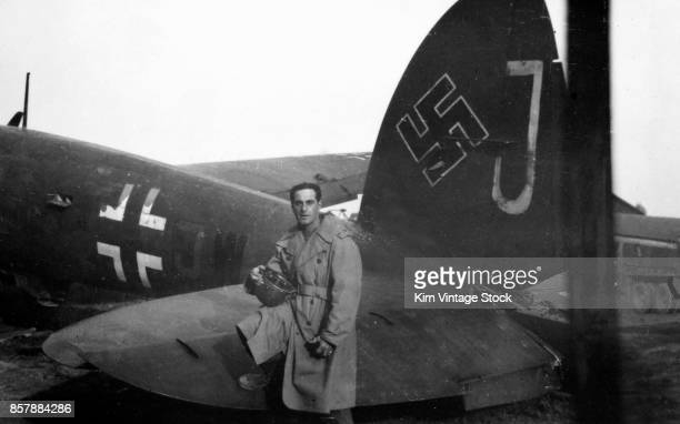 A US army soldier poses by the tail fin of a captured German plane during the liberation of France The plane has both swastika and luftwaffe markings