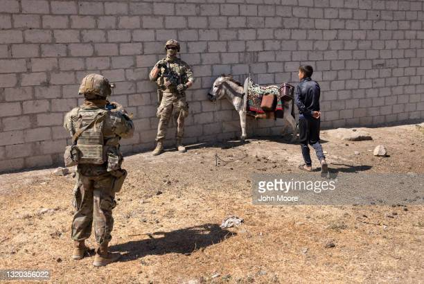 Army soldier poses for a photo with a donkey while visiting a village on patrol on May 26, 2021 near the Turkish border in northeastern Syria. U.S....
