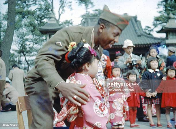 A US Army soldier poses for photographs with a girl dressed in kimono as people make the 'Hatsumode' first visit to the shrine at Yasaka Jinja Shrine...