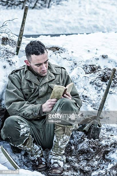 wwii us army soldier praying while reading new testament bible - soldier praying stock photos and pictures